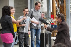 Jongeren die aan het project deelnamen worden geïnterviewd op het podium.
