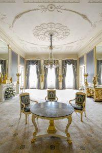 Balkonkamer van Paleis Noordeinde. Te zien is een tafel met omringend blauw beklede stoelen en erboven een kroonluchter.
