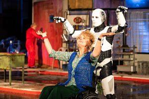 Vrouw in rolstoel met achter haar een robot.