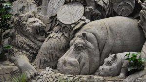 Zandsculptuur van een leeuw, vogel en nijlpaarden.
