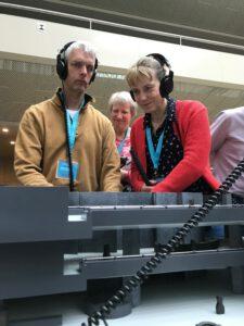 Mensen met een visuele beperking luisteren aandachtig naar de audiomaquette.