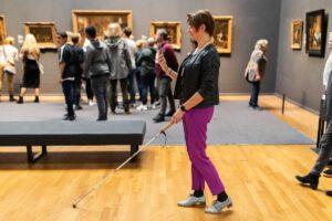 Blinde vrouw navigeert door Rijksmuseum met taststok en een smarthphone