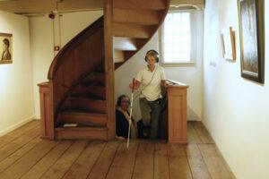 Blinde vrouw loopt door het Voerman Museum Hattem terwijl ze luistert naar de 3D-audiotour.