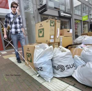 Blinden man met geleide stok volgt geleide lijn en loopt op tegen dozen en vuilnis.