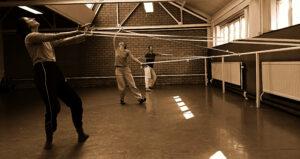 Dansers in een studio in de weer met lange linten.
