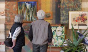 Twee oudere bezoeker bekijken schilderijen in het Cobra Museum