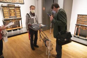 Blinde man met draagbare maquette om en zijn blinde geleide hond aan de lijn. Hij wordt geïnterviewd.