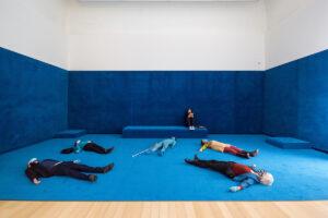 Sightless seeing toour waar mensen op de grond liggen in de expositiezaal.