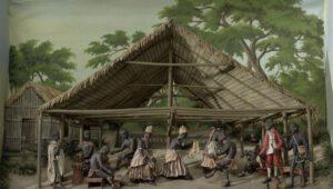 Inheemse groep mensen in hut.