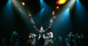 Scene uit het stuk de Great Bean. Man met twee brandende fakkels omringt door dansers in zwarte tutu's.