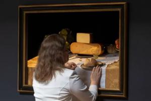 Vrouw betast schilderij met etenswaren met haar handen
