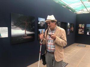 Hannes Wallrafen staat centraal in beeld en kijkt naar zijn smartphone. Op de achtergrond zijn de foto's van zijn expositie te zien.