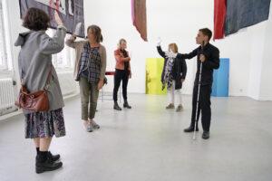 Blinde acteur leidt mensen door een ruimte.