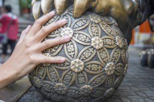 Grote gouden bol met klauw die wordt verkend door een hand.