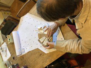 Man verkent plattegrond en prototypes van de Tweede Kamer met zijn handen.